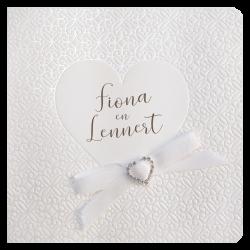 Klassieke trouwkaart met sierlijk parelmoerpatroon, een hart in reliëf en luxe strik met een strass stenen hart erop.